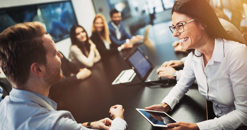 Des collègues souriants dans une salle de réunion moderne