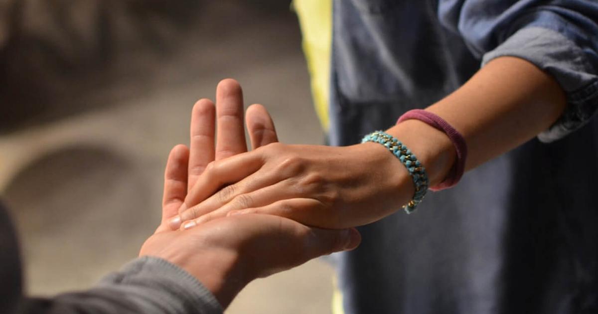 Twee mensen houden handen.