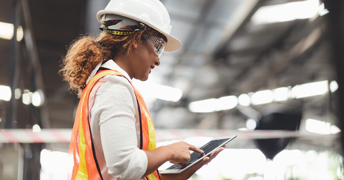 Une femme travaille dans la construction avec l'iPad