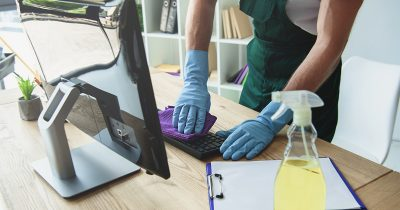 Persoon die computertoetsenbord schoonmaakt