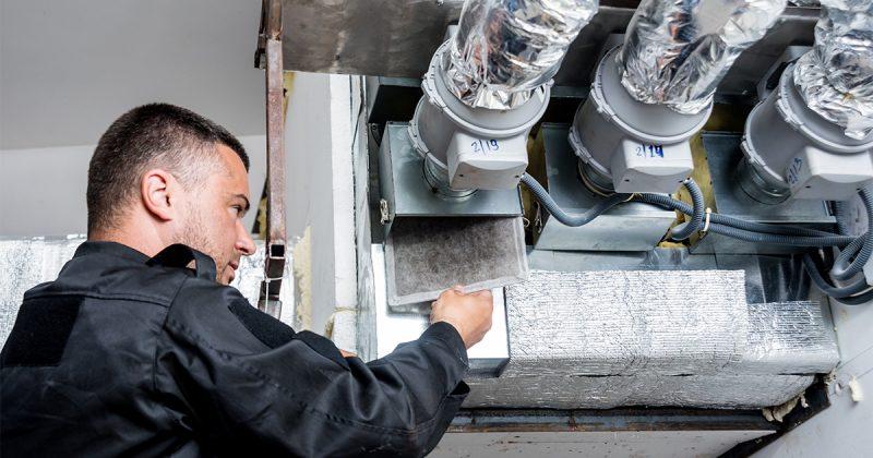 Tekniker byter filter för luftkonditionering