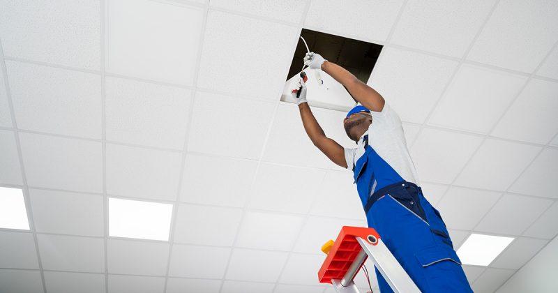 Arbeiter repariert Deckenbeleuchtung