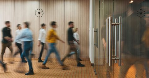 People in lobby entering and leaving building