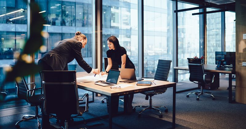 Kollegen, die über einem Schreibtisch arbeiten