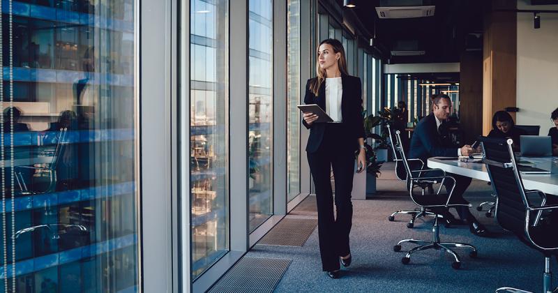 Lady in office walking past window